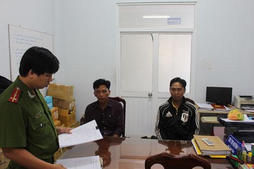 Huỳnh Văn Giàu và Phạm Quang Phương Đoàn nghe cán bộ công an đọc quyết định khởi tố bị can