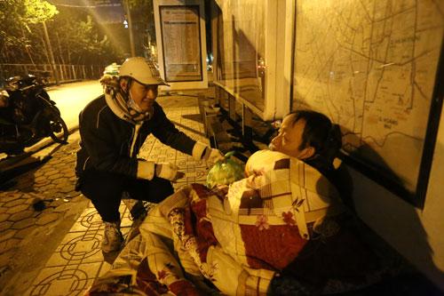 Một bạn trẻ ở Hà Nội tặng chăn ấm và đồ ăn cho người tá túc qua đêm tại hè phố Ảnh: Văn Duẩn