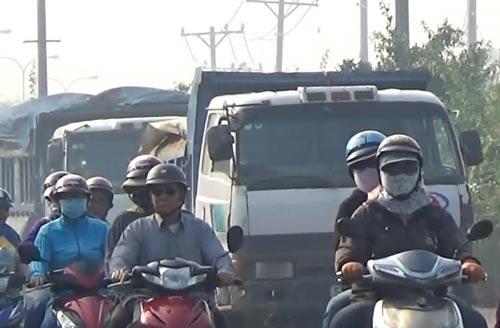 """Hai chiếc xe ben đang """"đua"""" trên Quốc lộ 22 (đoạn qua xã Tân Phú Trung, huyện Củ Chi), bất chấp các phương tiện khác đang lưu thôngẢnh: Lê Phong"""