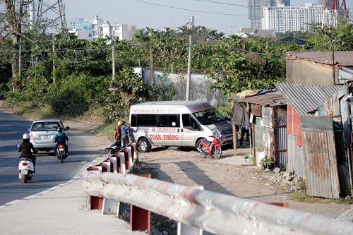 Nhà xe Toàn Thắng vô tư tận dụng đường bên hông cầu Cá Trê 1 (quận 2, TP HCM) làm bến cóc đón - trả khách và bốc dỡ hàng hóa Ảnh: QUỐC CHIẾN