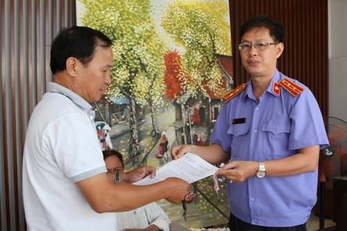 Đại diện VKSND huyện Bình Chánh, TP HCM trao quyết định đình chỉ bị can đối với ông Nguyễn Văn Tấn Ảnh: HỒNG QUANG