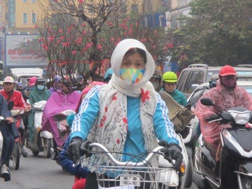Người dân Hà Nội phải mặc áo ấm rất dày, đeo găng tay và bịt khẩu trang khi ra đường vào chiều 22-1 Ảnh: Văn Duẩn