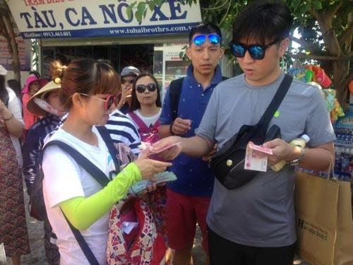 Trao đổi đồng nhân dân tệ cho du khách Trung Quốc tại cảng Cầu Đá, TP Nha Trang Ảnh: HOÀNG TÂN