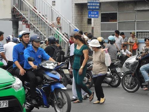 Bất chấp nguy hiểm, nhiều người vô tư băng qua đường thay vì đi trên cầu vượt Nơ Trang Long (quận Bình Thạnh). Ảnh: QUỐC CHIẾN
