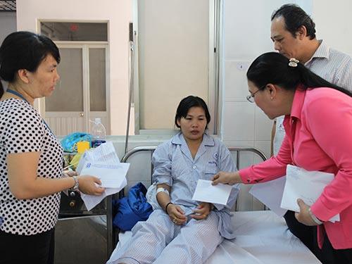 Bà Nguyễn Thị Bích Thủy, Phó Chủ tịch LĐLĐ TP HCM (bìa phải), thăm hỏi công nhân Công ty Pou Yuen bị tai nạn giao thông