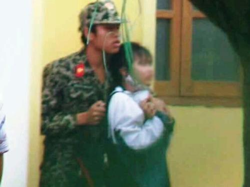 Kẻ trong trang phục quân nhân đang khống chế nữ sinh trường Cao đẳng Y Thái Bình - Ảnh: Facebook