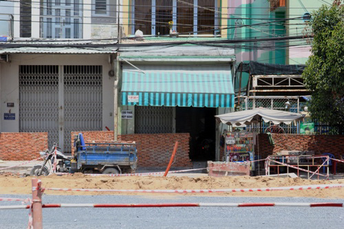 Bức tường cao hơn đầu người sừng sững chắn trước cửa nhà dân trên đường Kinh Dương VươngẢnh: Sỹ Đông