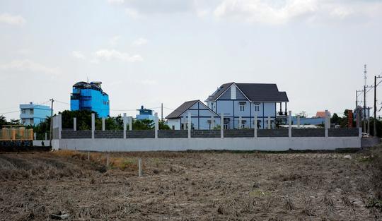 Một căn biệt thư đã hoàn thành, kế bên là một móng nhà đang xây dựng nằm trên đất ruộng tại ấp 4, xã Đa Phước, huyện Bình Chánh. Ảnh chụp trưa 11-5 Ảnh: MINH THANH