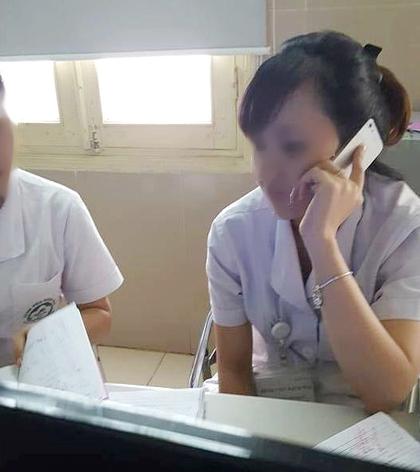 Nữ nhân viên gọi điện thoại di động khá lâu trong khi thời điểm đó đang có nhiều bệnh nhân xếp hàng đứng chờ - Ảnh: Facebook