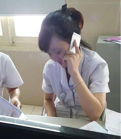Nữ nhân viên y tế buôn điện thoại trong giờ làm việc và nhiều người đang xép hàng chờ - Ảnh: Facebook