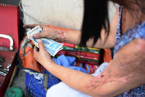 Chị Vũ Thị Loan mỗi ngày bơm vá xe ở ngã tư đường để nuôi sống cả nhà