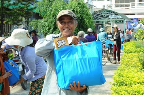 Ông Nguyễn Văn Châu, 63 tuổi, cười tươi sau khi nhận quà tại trụ sở UBND thị trấn Châu Ổ