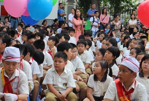 Một giáo viên lặng lẽ quạt cho học sinh trong lễ khai giảng sáng 5-9 tại Trường Tiểu học - THCS -THPT Nam Sài Gòn Ảnh: Bảo Lâm