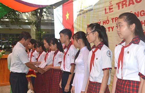 ông Nguyễn Hoàng Dũng, Phó Tổng Giám đốc thứ nhất của Công ty TNHH Phát triển Phú Mỹ Hưng, trao học bổng cho các em học sinh