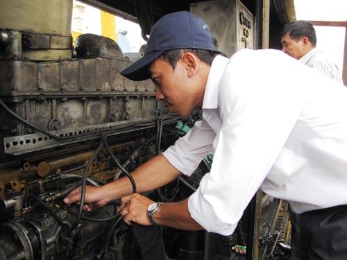 Kỹ sư Huỳnh Tuấn Dũng kiểm tra hoạt động của bảng điều khiển động cơ máy nâng dỡ hàng