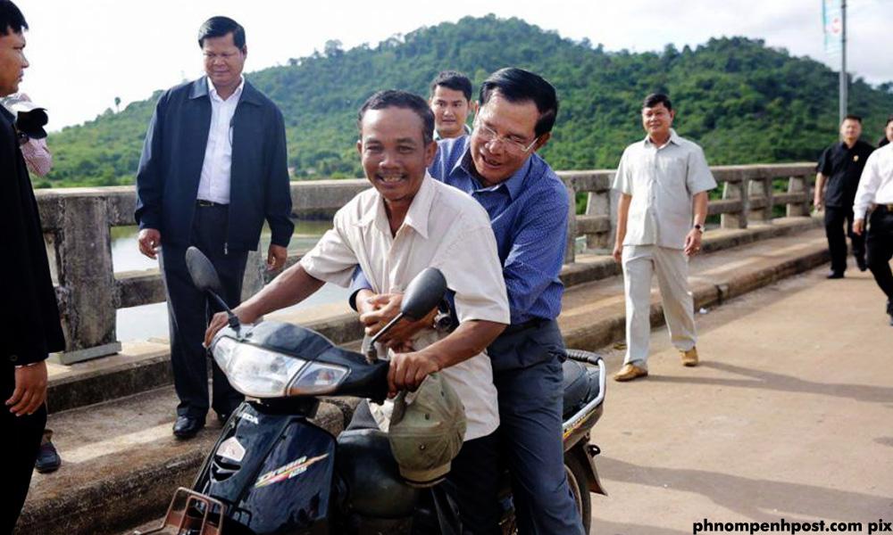 Thủ tướng Hun Sen đi xe máy không đội mũ bảo hiểm. Ảnh: Phnompenh Post