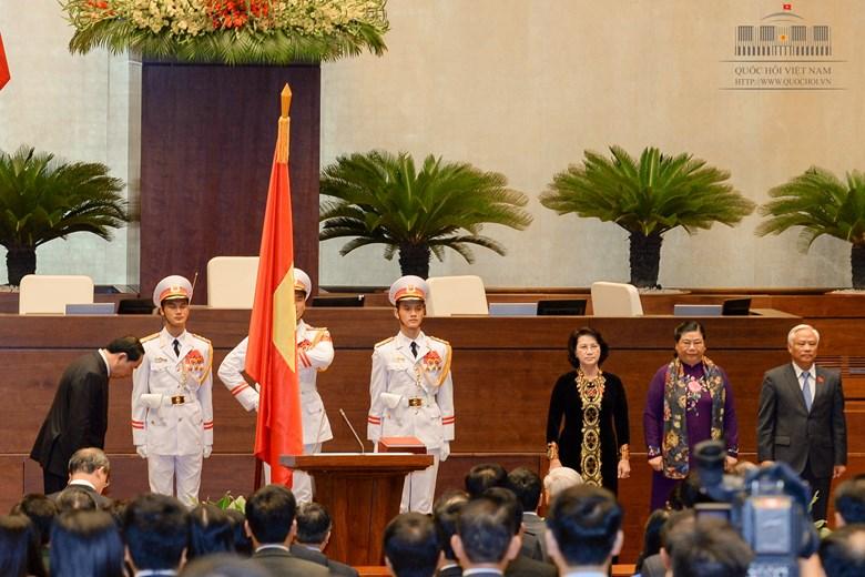 Chủ tịch nước cúi đầu trước cờ đỏ sao vàng trước khi tuyên thệ - Ảnh: Quochoi.vn