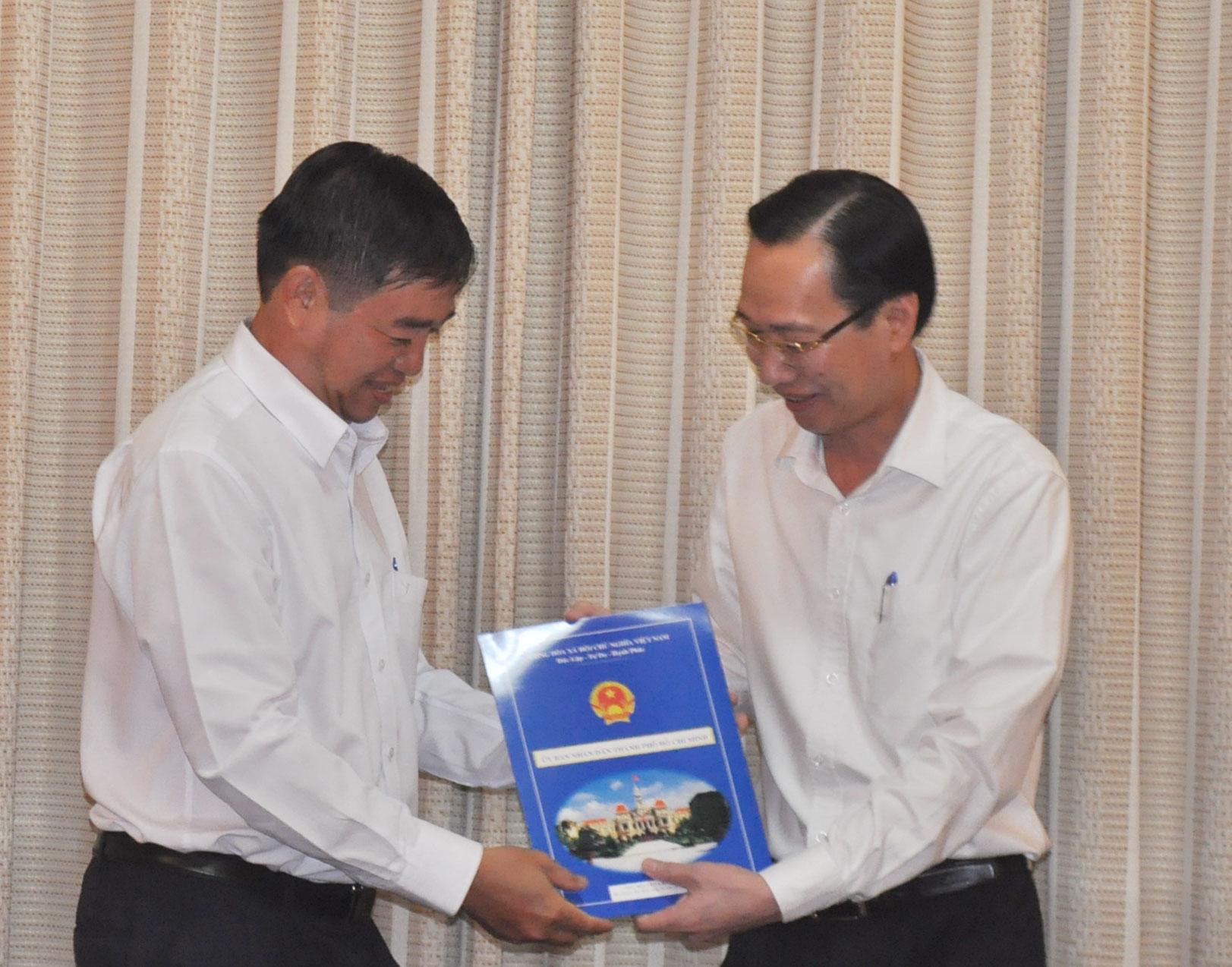 Phó Chủ tịch UBND TP Lê Thanh Liêm (bìa phải) trao quyết định điều động, bổ nhiệm cho ông Nguyễn Văn Trường