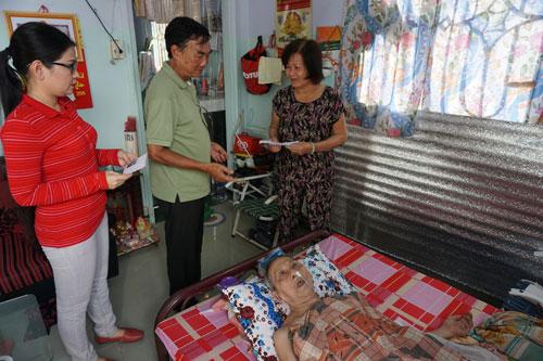 NSƯT Hồ Ngọc Trinh và nhạc sĩ Trương Minh Châu (từ trái sang) trao tiền giúp đỡ nhạc sĩ đàn tranh Lâm Nghĩa