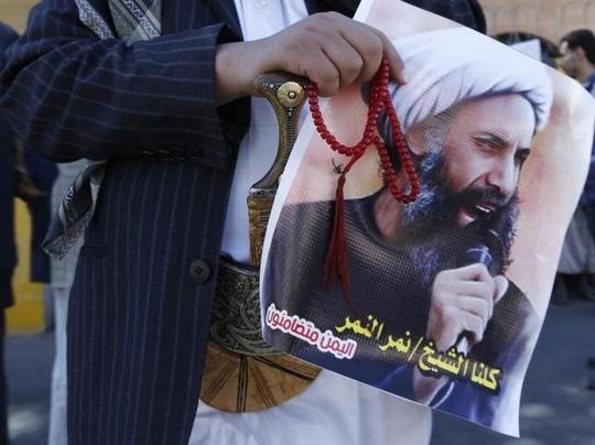 Người biểu tình cầm di ảnh của giáo sĩ nổi tiếng Nimr al-Nimr. Ảnh: Reuters