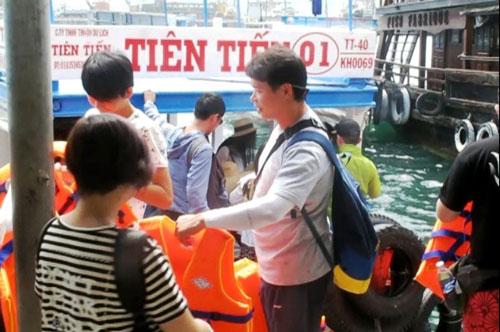Một hướng dẫn viên du lịch người Trung Quốc hướng dẫn khách tại cảng Cầu Đá (Nha Trang) vào sáng 29-6  Ảnh: Hồng Ánh