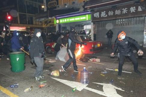 Người biểu tình tấn công cảnh sát. Ảnh: SCMP