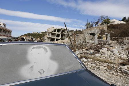 Hình ảnh Tổng thống Syria Bashar al-Assad trên kính một chiếc ô tô đỗ trước những ngôi nhà đổ nát ở thị trấn Rabiya, sau khi quân chính phủ tái chiếm thị trấn ở tỉnh duyên hải Latakia này. Ảnh: Reuters