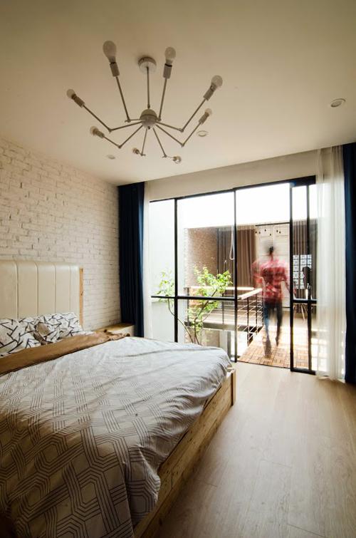 Phòng ngủ chính sử dụng hệ cửa kính lớn tạo cảm giác rộng rãi và có rèm để đảm bảo riêng tư khi cần.