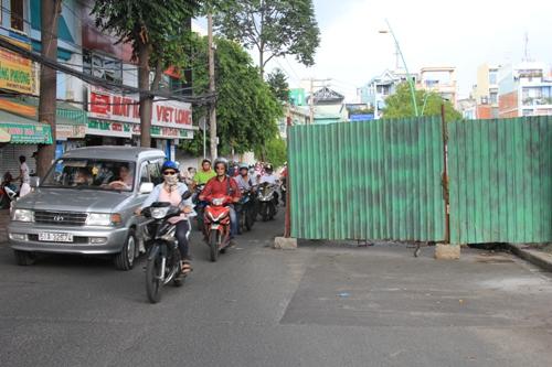 Do mặt đường bị chiếm dụng một nửa để lập hàng rào nên gây khó khăn cho các phương tiện khi lưu thông qua đây