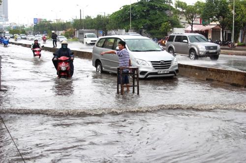 """Mỗi khi có ô tô đi qua, nước lại tràn vào nhà nên ông Tuấn phải dựng chiếc ghế gỗ ra ngoài đường với hy vọng xe ô tô sẽ chạy chậm lại nhưng không hạn chế được bao nhiêu. """"Mới mưa nhỏ đầu mùa mà đã ngập như thế này, thì những con mưa tiếp theo kết hợp với triều cường chắc người dân khó sống"""" – ông Tuấn ngao ngán."""