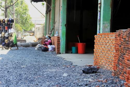 Vật liệu xây dựng và bức tường chắn phía trước làm cuộc sống của nhiều hộ dân ở đây trở nên khó khăn hơn