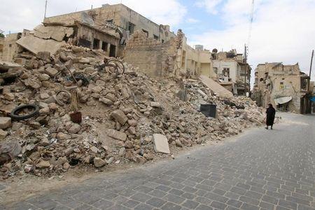 Một phụ nữ đi ngang những tòa nhà đổ nát ở Aleppo. Ảnh: REUTERS