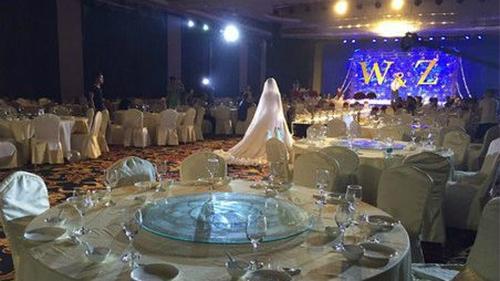 Cô dâu đang đứng trong hội trường một đám cưới trống không, chỉ có vài người nhà hai bên gia đình.