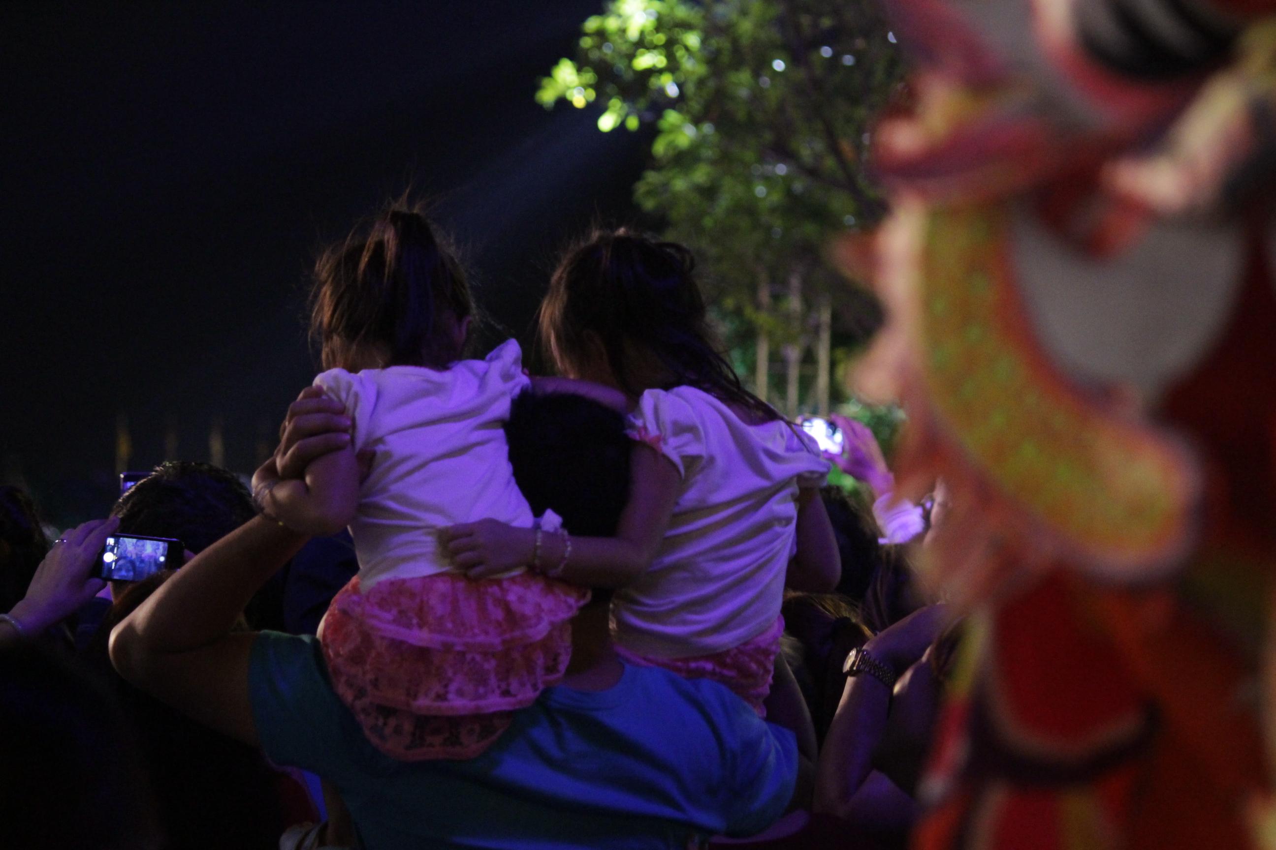 Các em nhỏ được bố mẹ công kênh trên vai háo hức, say mê theo dõi màn bắn pháo hoa.