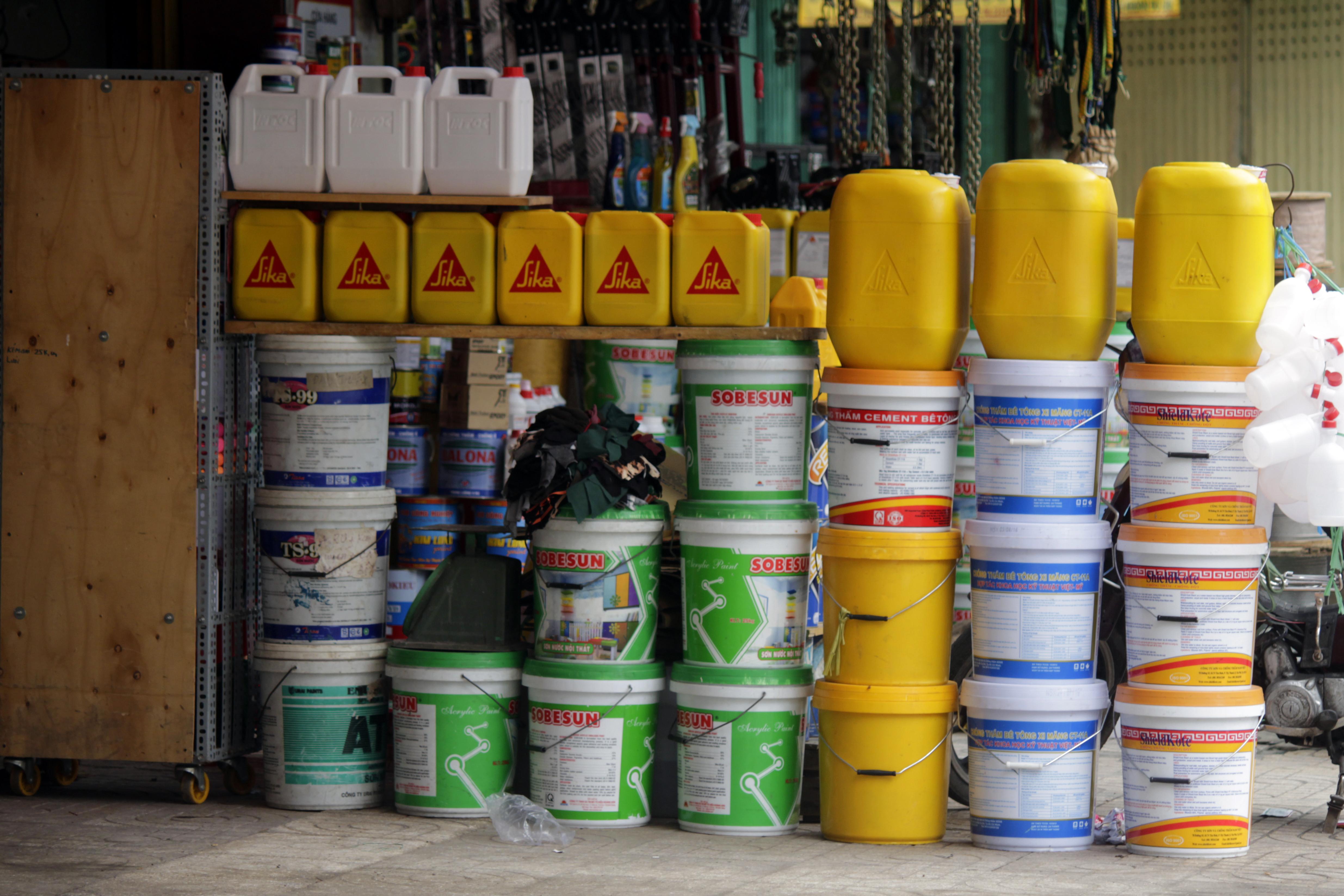 Hóa chất công nghiệp, sơn, màu nhuộm, hóa chất độc hại được chứa trong các can thùng chất đống trên vỉa hè để chào mời khách hàng. Nhiều thùng hóa chất có nhãn mác bằng chữ Trung Quốc.