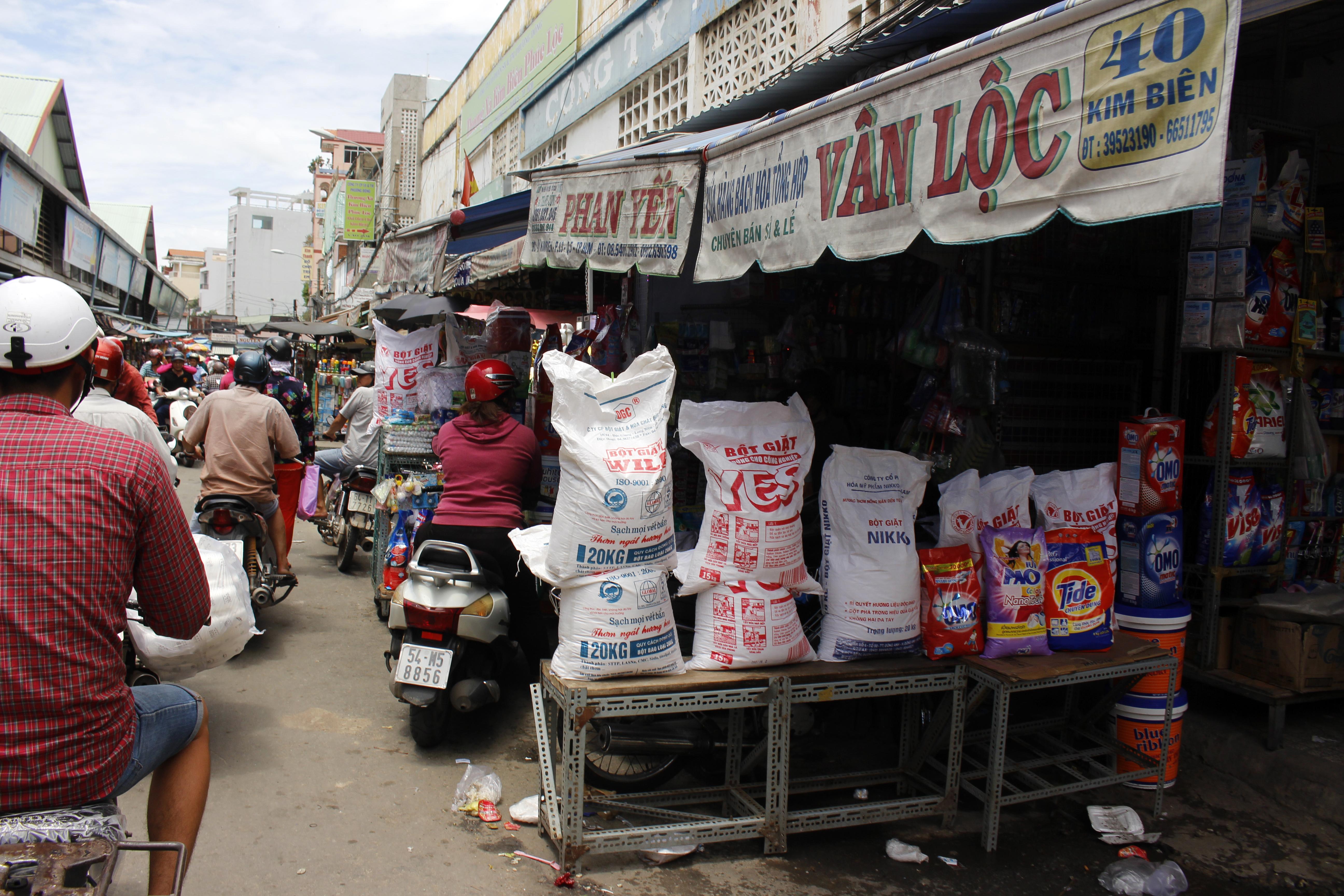 Chỉ tính hai bên mé chợ đã có khoảng 16 cửa hàng kinh doanh hóa chất, hương liệu được đựng trong các thùng, bao, can, xô nhựa lấn ra đường. Khách hàng cũng dừng xe tới mua hàng nhộn nhịp khiến nơi đây luôn chật chội, ùn tắc.