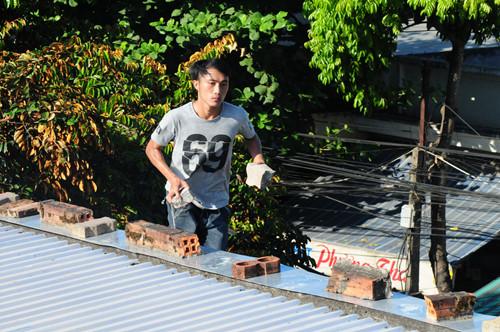 Một thanh niên ngáo đá cố thủ trên nóc nhà nhiều giờ liền và dùng gạch đá ném tứ phía