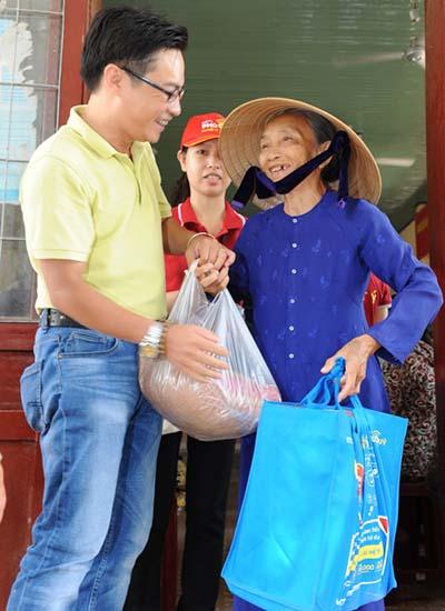 Nhạc sĩ Xuân Nghĩa, đại diện Báo Người Tiêu Dùng, đang phát quà và thăm hỏi người dân đến nhận quà