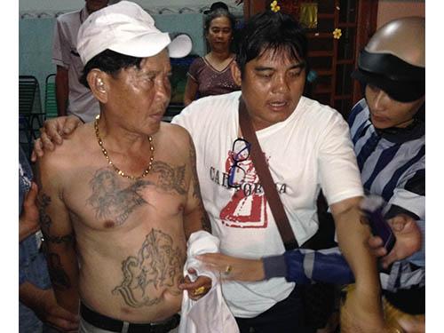 """Lê Duy Khánh (bìa trái) bị các """"hiệp sĩ"""" đưa về Công an phường Phú Lợi, TP Thủ Dầu Một, tỉnh Bình Dương"""