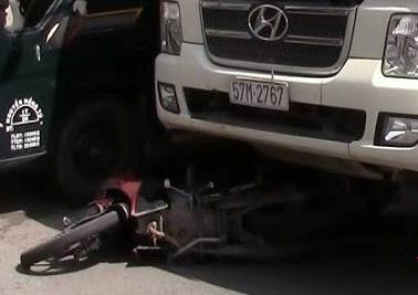Xe máy bị cuốn vào gầm, còn cô gái bị bánh xe cán qua chân, kêu la thảm thiết