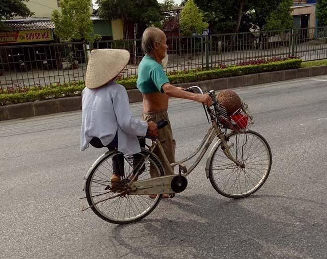 Cụ ông ngoài 80, đầu trần, chân đất dắt vợ trên xe đạp cả quãng đường gần 2 km đi bán mít. Ảnh: Minh Hiếu.