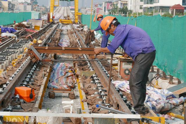 Công nhân đang lắp đặt cố định đường ray với các ốc bu lông
