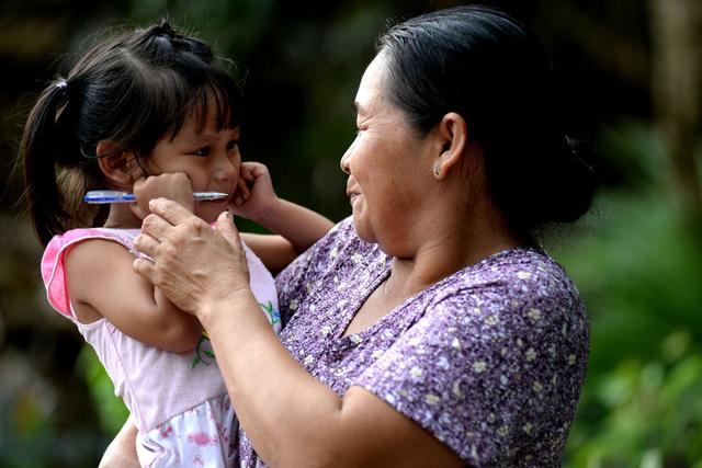 """Bà Nguyễn Thị Hồng Tư, bà ngoại bé Lan Anh tâm sự: """"Dù đã thân thiết với gia đình, nhưng cháu ngoại tôi vẫn còn khá rụt rè khi mọi người tới thăm""""."""