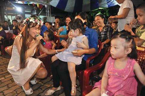 Các bé kết tặng Tổng giám đốc Vietjet vòng hoa xinh xắn. Chị cất lên giọng hát ngọt ngào ca khúc Mẹ yêu con và dịu dàng đến bên từng bé