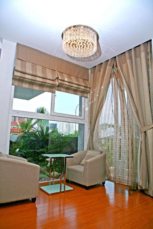Một góc phòng ngủ với ghế sofa vuông dùng để cà phê sáng, nơi có thể nhìn ra ngoài khoảng lan can đầy hoa lá.