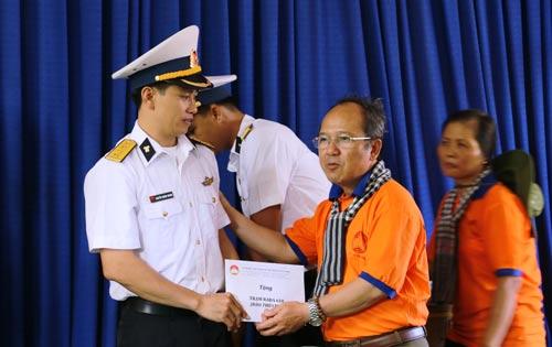Đại úy Nguyễn Hoàng Quang (bên trái) nhận quà từ đoàn đại biểu TP HCM