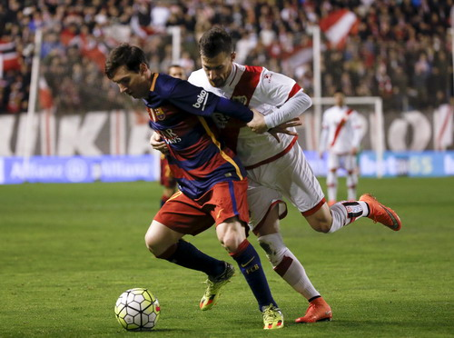 Messi đi bóng trước sự truy cản của hậu vệ Tito