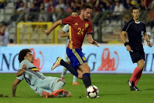 Saul Niguez tranh chấp bóng với Axel Witsel (trái)