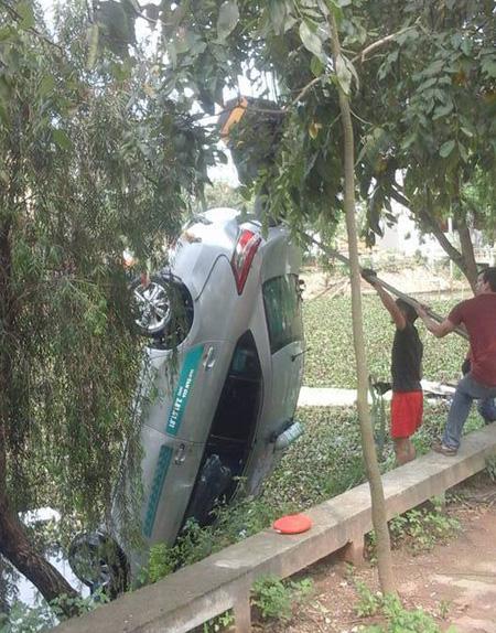 Lực lượng chức năng tiến hành trục vớt chiếc xe taxi - Ảnh: Facebook