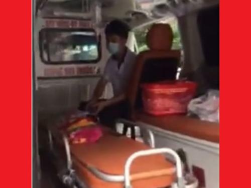 Trong khi bảo vệ chặn xe cứu thương thì trên xe, cháu bé đang được một nhân viên y tế bóp bóng duy trì sự sống. (Ảnh cắt từ clip)